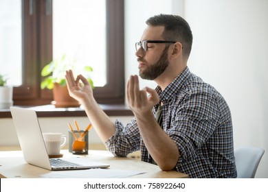 Millennial male manager practicing yoga meditation with eyes closed on working place. Bearded businessman in casual taking rest for wellness, stress control and mental health