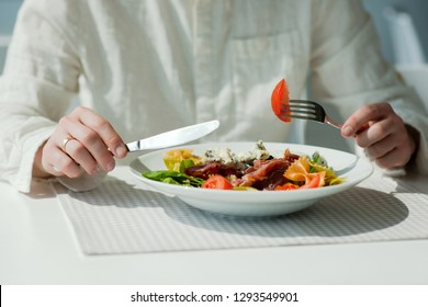 Millennial male no face having vegetables, healthy eating and lifestyle concept. Unrecognizable man eat organic food in office. Hand hold fork with tomatoes. Adult has lunch with fresh greek salad
