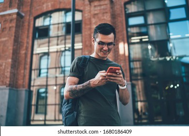 Millennial man sending text review about application for playing online games connected to 4g wireless on cellphone during leisure time outdoors, positive Caucasian male blogger chatting via app