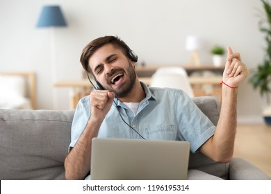 Millennial man sitting on couch in living room at home sing a song using laptop and headset moving in rhythm with favourite music. Male feels cheerful mood listening popular tracks online on internet