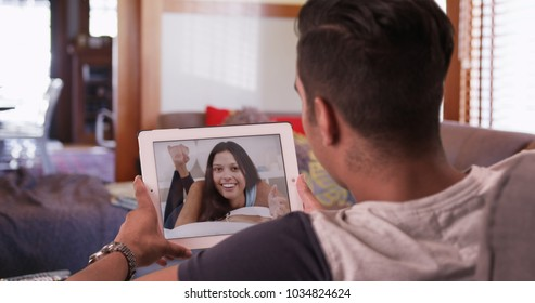 Millennial man video chatting or having a facetime conversation with his girlfriend on tablet computer