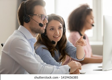 Millennial man and woman wearing headset work together training on pc in shared office, female call center agent in earphones show help male colleague busy consulting customer on computer