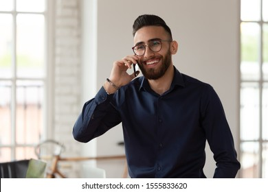 Millennial middle eastern ethnicity businessman talking on phone in office, young satisfied employee solve business issues during workday in modern workplace, successful entrepreneur portrait concept