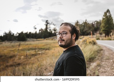 a millennial outdoors in the fall seasoned colored background. wearing eye glasses with a beard and long hair, looking happy smiling and relaxed outside
