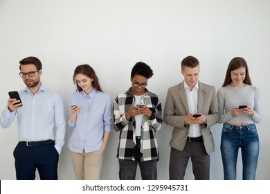 Millennial phone users business people group standing in row using smartphones, diverse customers holding cellphones looking on gadget waiting in line, mobile addiction social media lifestyle concept