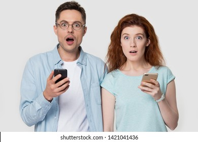 Millennial phones users shocked couple gawp look at camera pose on grey background unbelievable headlines online news, new free apps, shoppers received message big discount cheap tickets concept image
