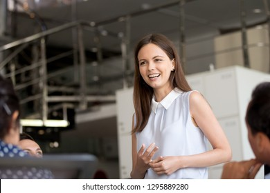 Millennial positive new employee introduces herself to colleagues has fist day in company. Young friendly coach talking with employees sharing knowledge discussing during meeting at office boardroom