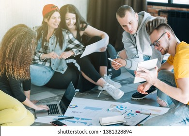Millennial IT specialists studying business strategy. Young people cooperating in modern loft room, sitting on floor.