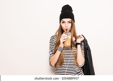 Millennial teenage girl drinking takeaway coffee, wearing modern black and white outfit.