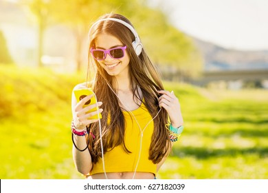 Millennial teenage girl in park on sunny day of spring or summer, with smart phone and headphones, texting and smiling. Closeup, medium retouch, vibrant colors, copy space.