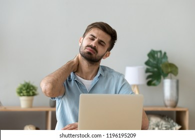 Millennial tired stressed man having a neck pain. Male touching massaging neck sitting at the desk working or studying indoors, suffering from discomfort long hours of sedentary overworking concept