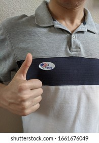 """Millennial voter showing his """"I voted"""" sticker while giving a thumbs up"""