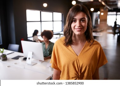 Millennial white female creative standing in a busy casual office, smiling to camera