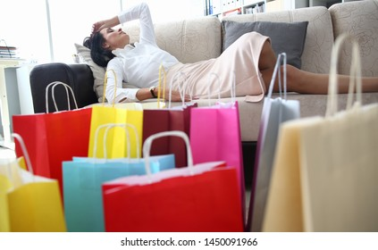 A millennial woman was shopping mall tired and fell asleep at home on couch. Many packages are in room front of sofa background. Shopaholic concept