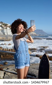 Millennial woman smiling for selfie taking photo with her phone cellphone mobile by the ocean