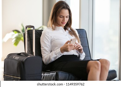 Millennial woman texting friends or writing email on smartphone while sitting with baggage in modern airport lounge, businesswoman go on business or work trip waiting for flight