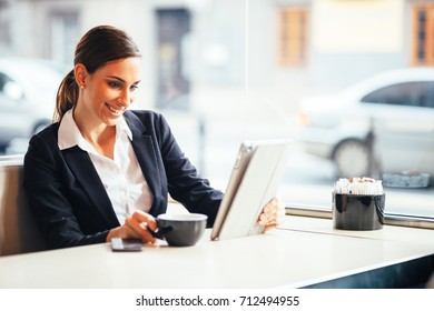 Millennial young businesswoman using tablet computer in coffee shop