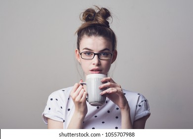 Millennial young woman in glasses with messy bun hairstyle, drinking coffee from a mug. Studio portrait of a gorgeous female model.