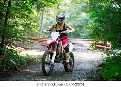 Millennial young woman riding big motocross bike in the forest