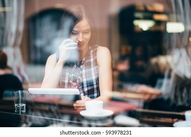 Millennial young woman talking on phone using tablet coffee shop