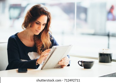 Millennial young woman using tablet computer in coffee shop