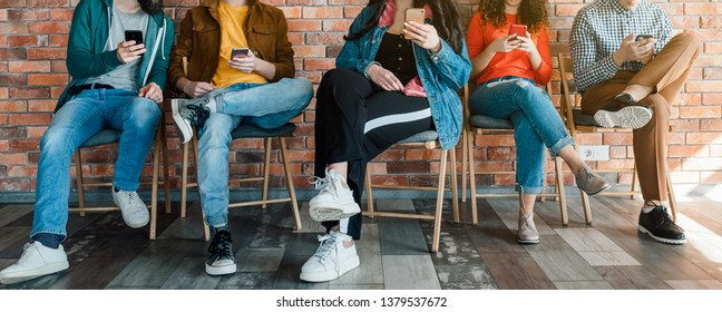 Millennials lifestyle. Group of young people sitting in modern loft office, using smartphones. Social media addiction.