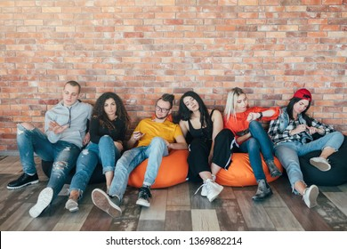 Millennials sitting around doing nothing in lounge zone. Young people resting in bean bags, getting bored without tasks at work.