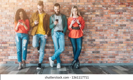 Millennials social media addicted generation. Young people in colorful outfits leaned against brick wall, using smartphones.
