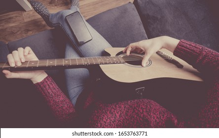 Millennials woman learns to play the guitar - online lesson on the internet - acoustic guitar. Subdued colors and shallow depth of field.