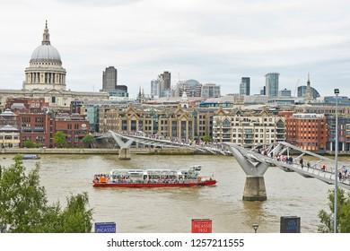 THE MILLENNIUM BRIDGE, THAMES EMBANKMENT, LONDON. AUGUST 2018. The Millennium Footbridge a suspension bridge over the River Thames with St Pauls and the skyline of the City of London.