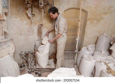 miller puts flour in a bag to weigh it on a balance in the corn mill