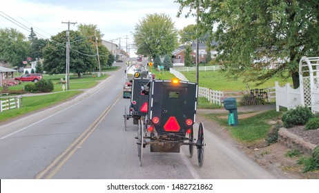 MILLERSBURG, UNITED STATES - OCTOBER 18th 2016: Amish horse-drawn buggy traveling along the street through bucolic town in Ohio, United States. Amish carriage driving along the road in scenic village