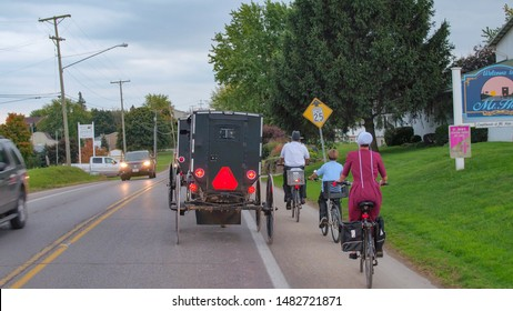 MILLERSBURG, UNITED STATES - OCTOBER 18th 2016: Amish family in traditional clothes riding bicycles along the street running through rural city, Ohio, USA. Amish people traveling through town in buggy