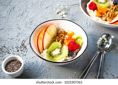 Millet in a bowl with fruits and chia seeds. Grey background.