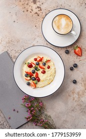 Millet porridge with strawberries and blueberries over beige concrete background with flowers and cup of cappuccino coffee. Healthy delicious breakfast. Top view, flat lay