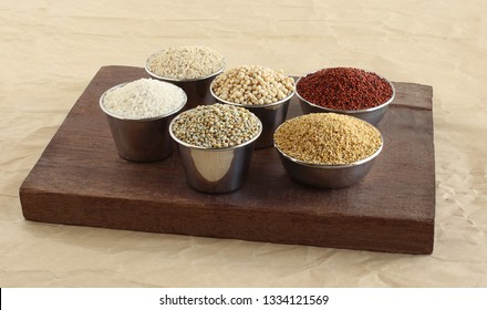 Millets, healthy vegetarian grains, including finger millet or ragi, foxtail millet, pearl millet or bajra, and kodo millet, in steel bowls.