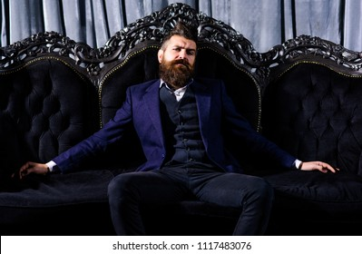 Millionaire in elegant suit sits on luxurious sofa. Bearded man with confident face in classic interior. Luxury lifestyle, confidence, success, rich, power, fashion, wealth, furniture, concept