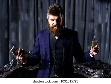 Millionaire in luxury suit smokes and holds money. Bearded man with calm face and cigar looks down. Rich, fashion, wealth concept. Brutal man with long beard has cigar, champagne and dollars.