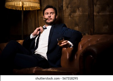 Millionaire man resting and relaxing while sitting on sofa in restaurant or men's club. Handsome man drinking whiskey and smoking cigar.