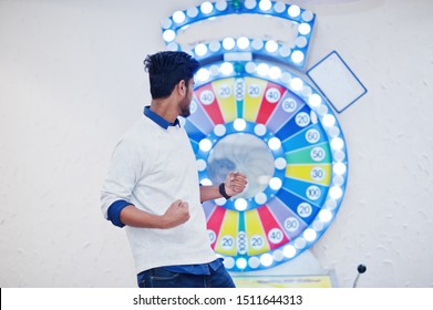 I'm a millionaire! Very excited young asian man against fortune wheel win at lottery great prize.