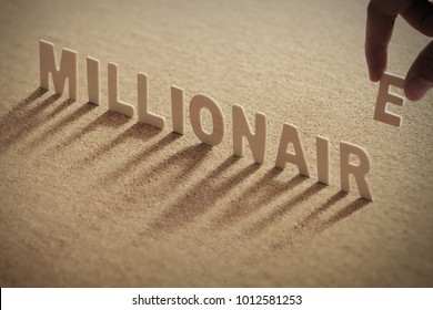 MILLIONAIRE wood word on compressed or corkboard with human's finger at E letter.