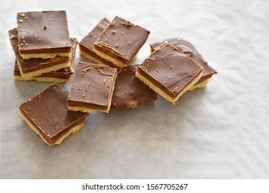 Millionaire's shortbread with chocolate and caramel on a parchment paper with copy space on the right bottom side.