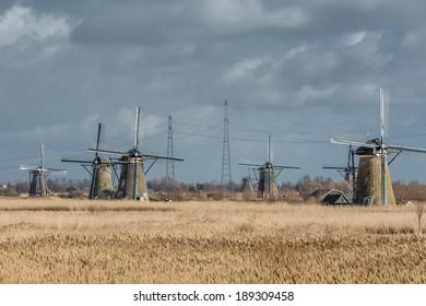 Mills against a dark cloudy sky at Kinderdijk Overwaard in the Netherlands, a Unesco heritage.