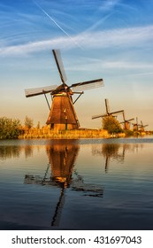 Mills in Netherland, Kinderdijk - scenic sunset landscape with windmills, blue sky and reflection in the water at soft light. Vertical image, nature background