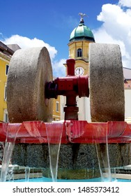 Millstone in a fountain and a city clock on a cultural monument in the background. Cultural and traditional heritage of the Croatian city of Rijeka