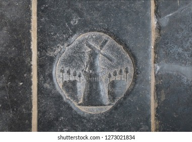a millstone on a tombstone on the floor of the Old Church in Amsterdam