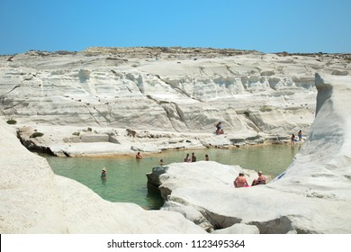 MILOS, GREECE-JUNE 6, 2017:  People swimming at Sarakiniko beach on Milos Island where the waves shape the greyish-white volcanic rock into amazing shapes, and the area is often compared to moonscape