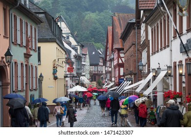Miltenberg, Bavaria / Germany - July 11 2019: American tourists doing a guided tour with red umbrellas in rainy town with half-timbered houses