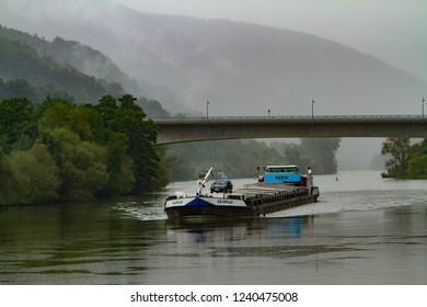 Miltenberg, Germany - 7/4/2013:  A commercial river boatcarrying freight, passes under a bridge on a foggy morning in Miltenberg, Bavaria, Germany