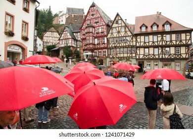 Miltenberg, Germany - 7/4/2013:  A tour group walking in the rain at city center in Miltenberg, Bavaria, Germany
